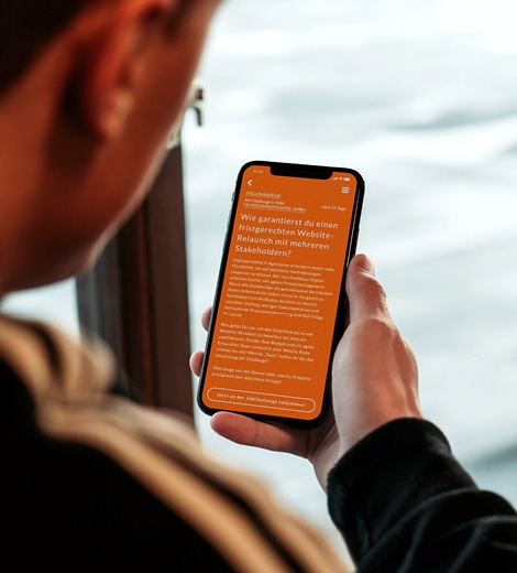 Mann hält Handy mit whyapply JobChallenge